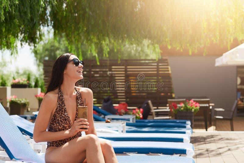 Außenaufnahme von Brunette gekleidet in Badeanzug mit dem Leoparddruck und -Sonnenbrille, die auf Ruhesessel und trinkendem frisc stockbild