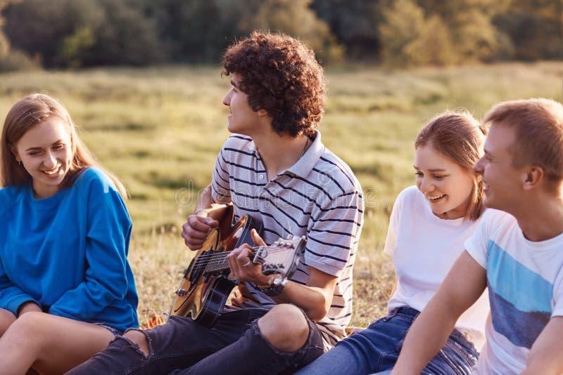 Außenaufnahme von den erfreuten netten Freunden oder von Begleitern, die in der guten Laune sind, singen Lieder von ihrer Kindhei stockfoto