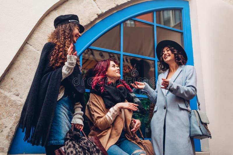 Außenaufnahme von drei jungen Frauen, die auf Stadtstraße plaudern und lachen Beste Freunde, die Spaß sprechen und haben lizenzfreie stockfotografie