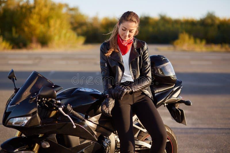 Außenaufnahme von erfreuten weiblichen Fahrrädern zieht die Lederhandschuhe, gekleidet in schwarze Kleidung, Haltungen auf Motorr lizenzfreies stockbild