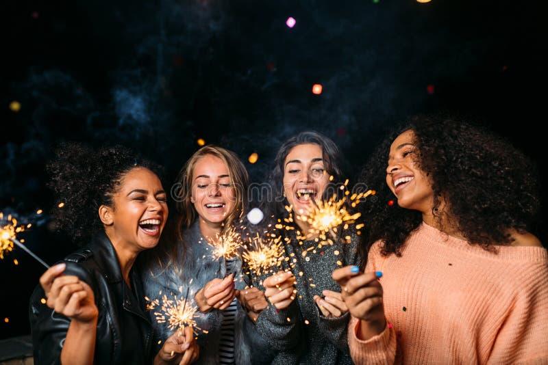 Außenaufnahme von lachenden Freunden mit Wunderkerzen stockbilder