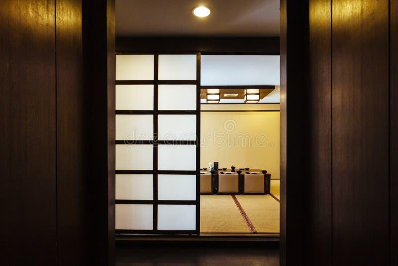 Außenseite des Esszimmers der japanischen Art mit Holztisch in der Mitte und in acht Kissensitzen verziert im Erdton lizenzfreie stockfotos