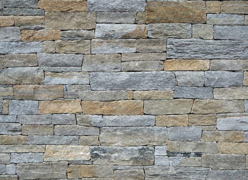 Außenwand hergestellt von den verschiedenen Formnatursteinziegelsteinen, mit Farben Braun und Grau Hintergrund und Beschaffenheit stockfotografie