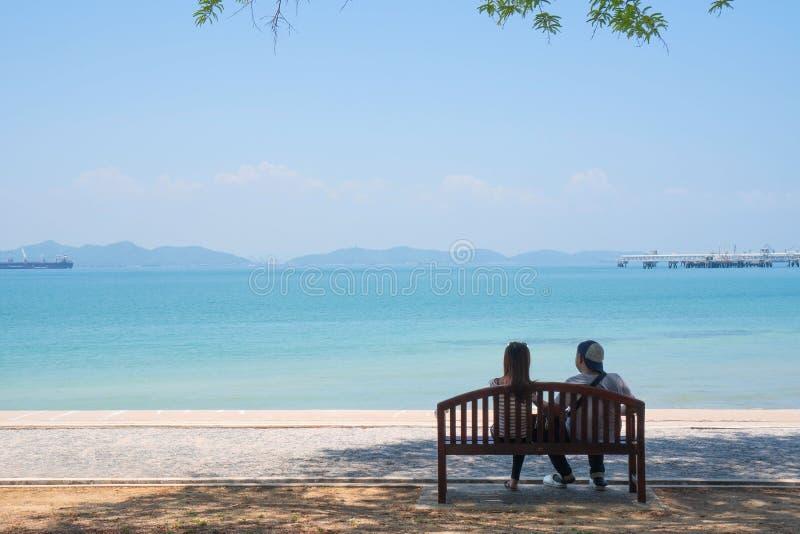 Au bord de la mer en été, jeunes couples heureux dans l'amour détendant des vacances de plage appréciant la vue d'océan se reposa photographie stock