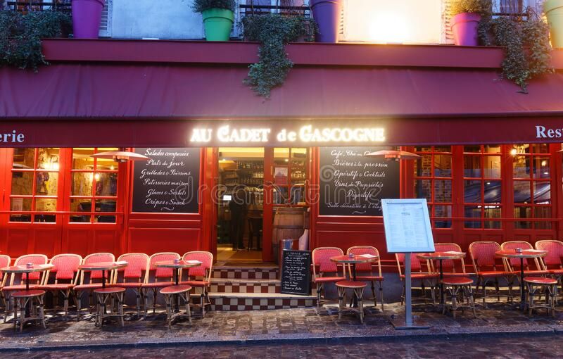 Au Cadet de Gascogne at rainy morning . It is a traditional French restaurant in the Montmartre district, Paris, France royalty free stock image