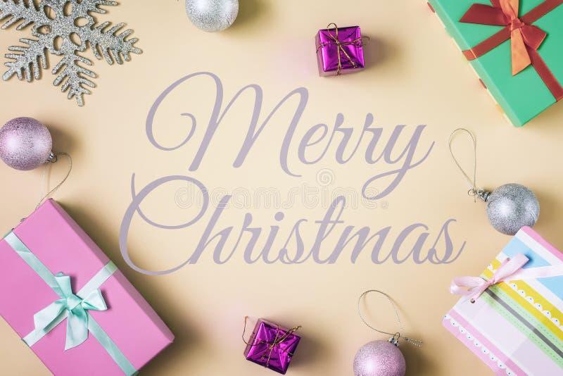 Au centre d'un fond beige, l'inscription est Joyeux Noël Écartez autour des boîtes avec des cadeaux et photographie stock libre de droits