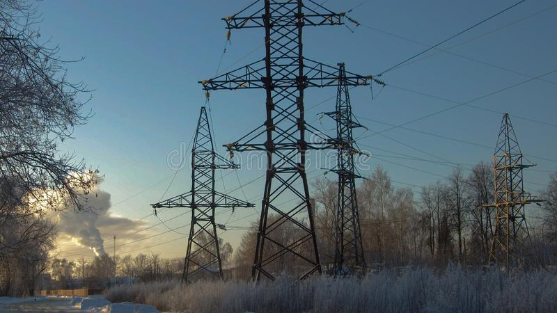 Au coucher du soleil en hiver, appui à haute tension image libre de droits