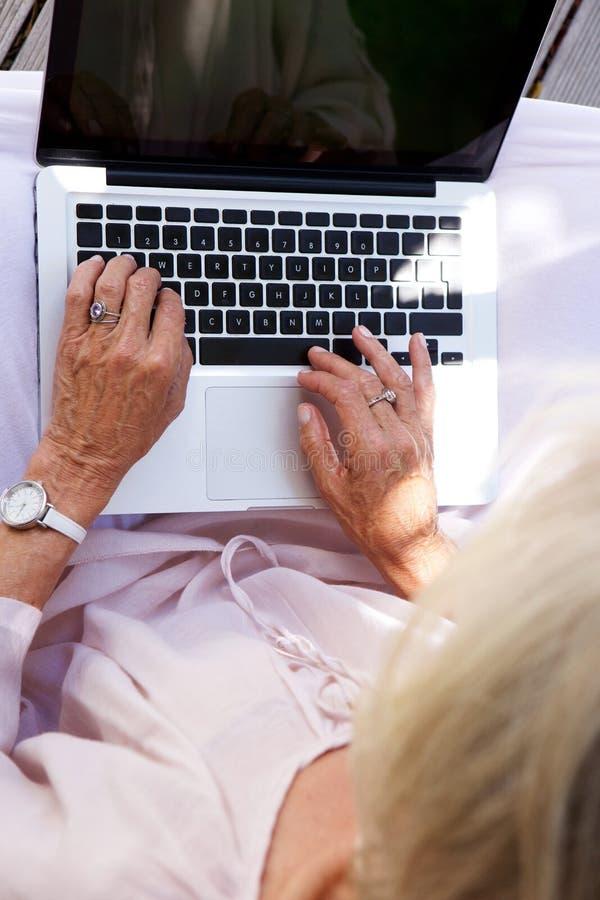 Au-dessus d'une femme plus âgée travaillant sur l'ordinateur portable image libre de droits