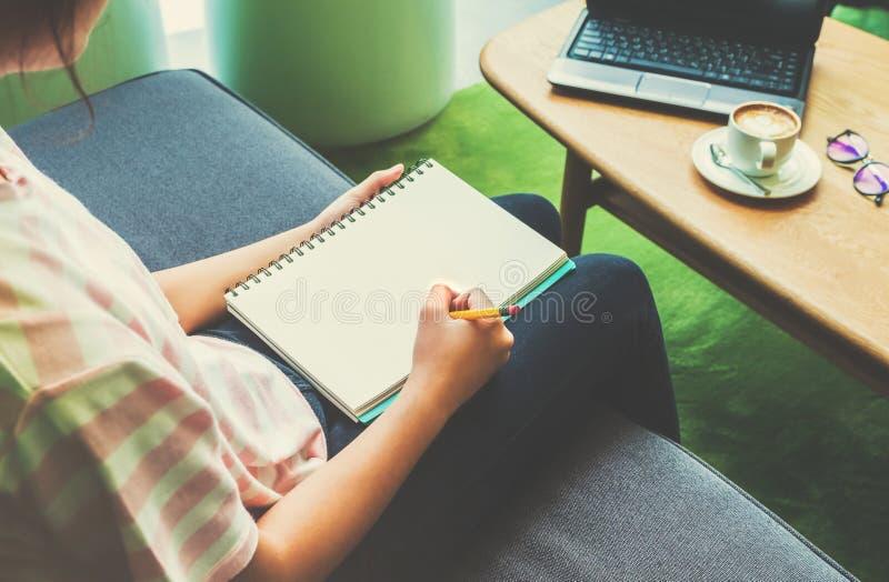 Au-dessus de l'épaule la vue a tiré de la jeune écriture de fille d'adolescent sur le notebo photos stock