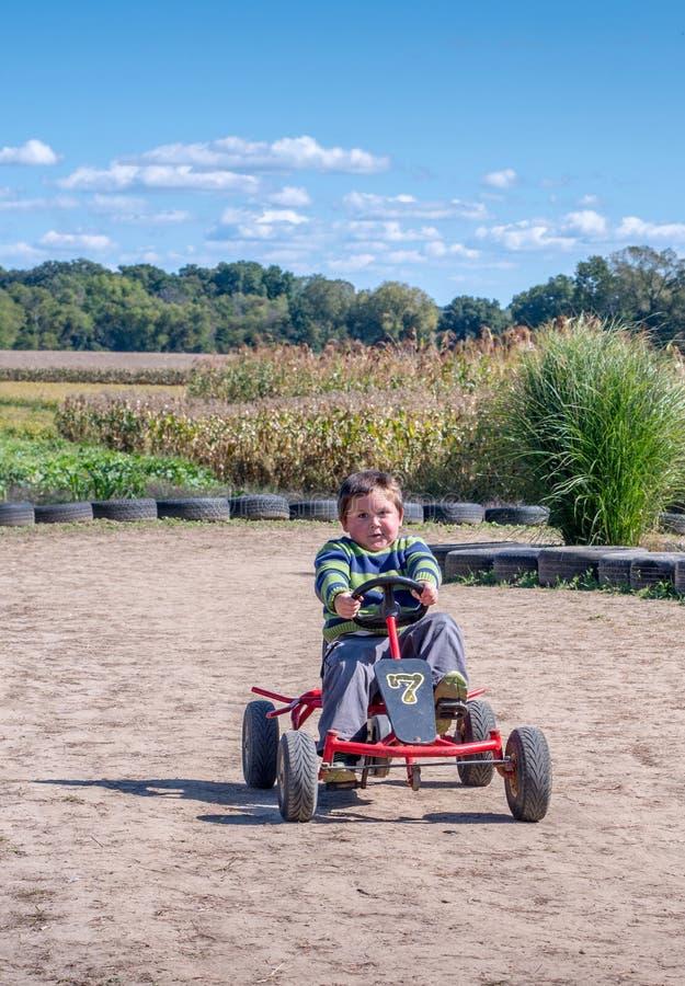 Au-dessus de l'enfant joyed a l'amusement conduisant une voiture de pédale autour d'une voie images libres de droits