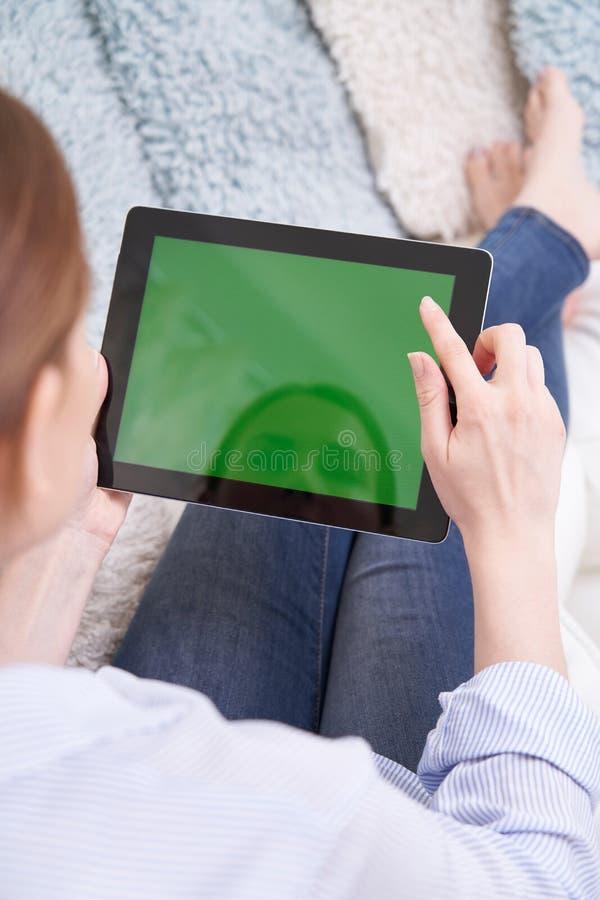 Au-dessus de la vue d'?paule de la femme se trouvant sur la Tablette de Sofa Using Green Screen Digital ? la maison photos stock