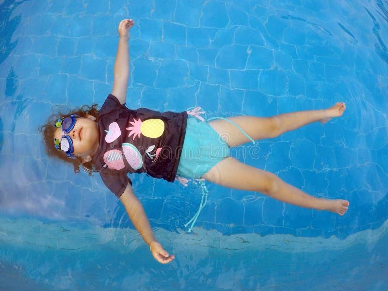 Au-dessus de la vue d'une jeune fille flottant dans une piscine photographie stock libre de droits