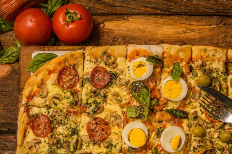 Au-dessus de la vue des tomates près d'une pizza délicieuse sur le fond en bois de table à la maison tout préparé image libre de droits