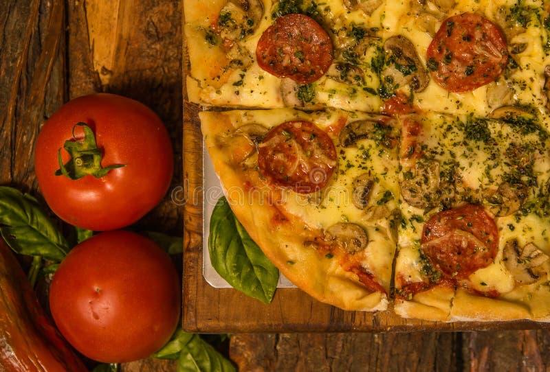 Au-dessus de la vue des tomates près d'une pizza délicieuse sur le fond en bois de table à la maison tout préparé photo libre de droits