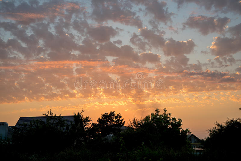Au-dessus des toits du beau coucher du soleil de maisons comme si tiré par un artist& x27 ; brosse de s, versée par différentes c photographie stock