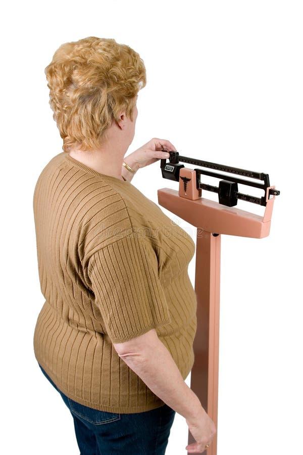 Au-dessus du regard d'épaule à une femme contrôlant son poids photographie stock