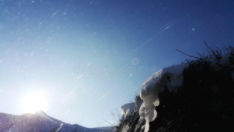 Au fond d'une falaise foncée nous recherchons une manière au soleil Les rayons du soleil font leur voie par la tempête de neige photographie stock