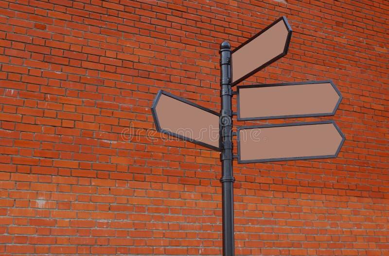 Au mur de briques rouge est une colonne de fer avec des flèches images libres de droits