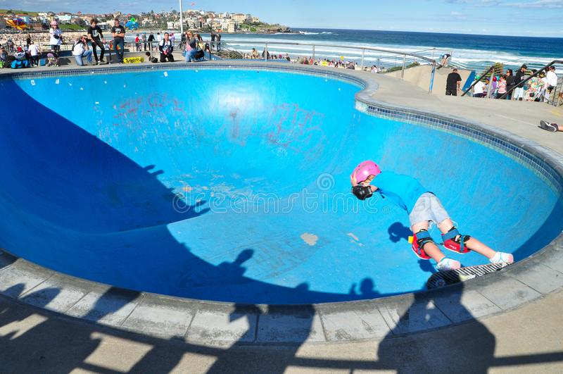 Au parc de patin près de Sydney, la plage de Bondi avec la petite fille montre la compétence de la planche à roulettes image libre de droits