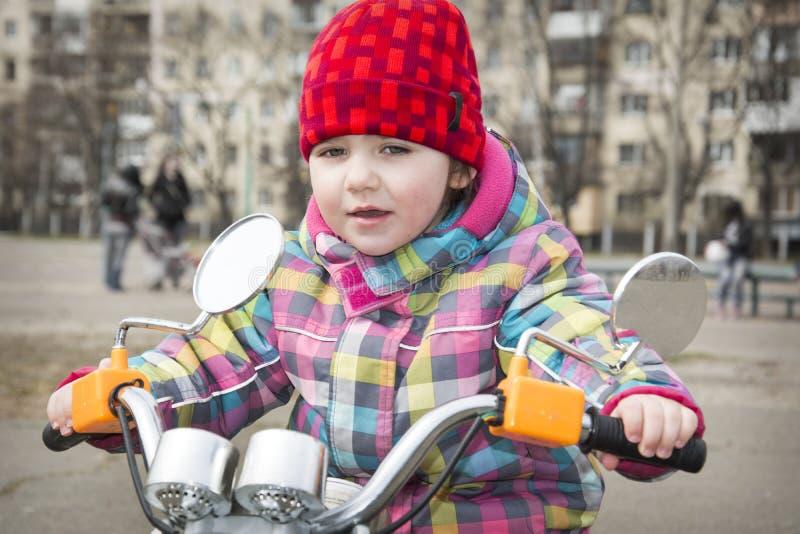 Au printemps d'une petite fille montant une moto sur la rue photos stock