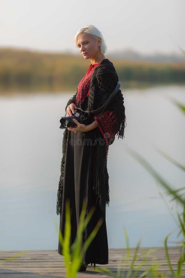 Au printemps, une belle femme dans une robe brodée par Bourgogne se repose sur un pilier en bois près de l'eau calme avec une cam images libres de droits