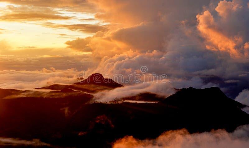 Aube orange sur la montagne Dessus de montagne dans les nuages photo libre de droits