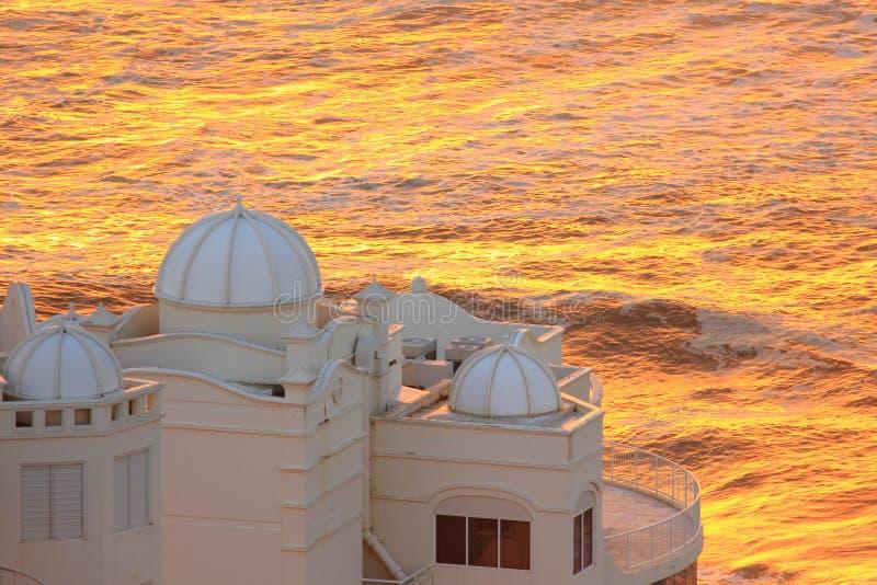 Aube se cassant au-dessus du palais à l'océan images libres de droits