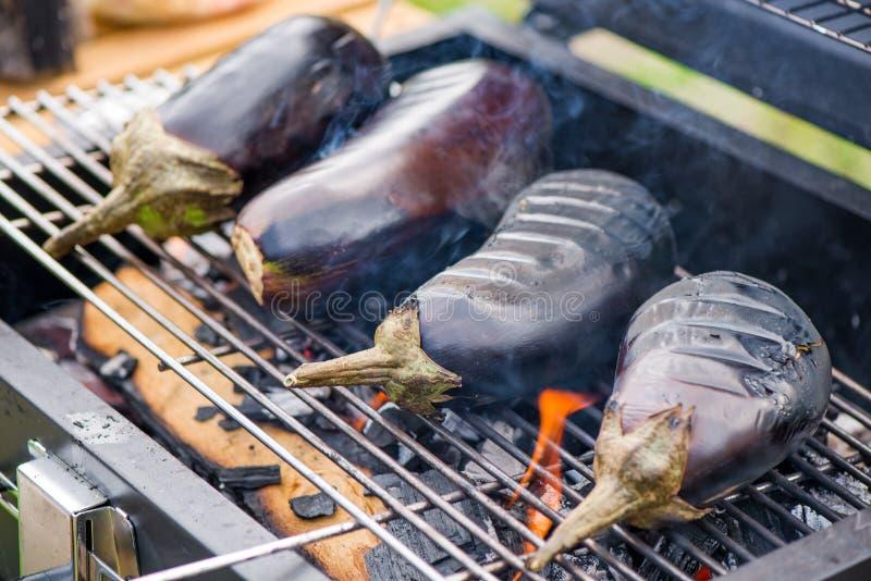 Aubergine bij de barbecuegrill op hete houtskool en brand stock afbeeldingen