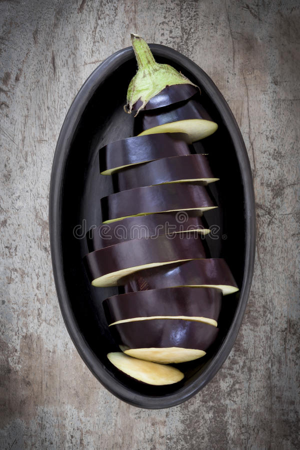 Aubergine coupée en tranches dans le plat noir photographie stock libre de droits