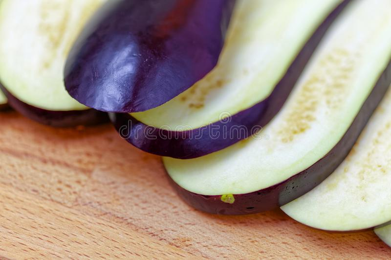 Aubergine or eggplant with slices on wooden background. Close up stock photography
