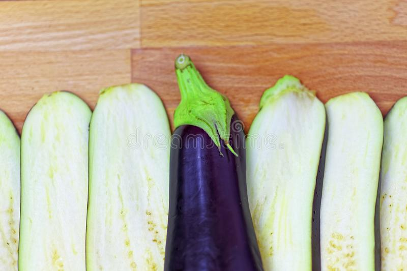 Aubergine or eggplant with slices on wooden background. Close up royalty free stock image