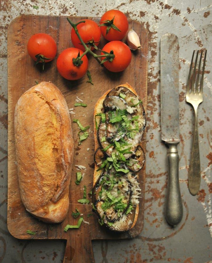 Aubergine en kaassandwich met tomaten op een uitstekende achtergrond stock afbeelding