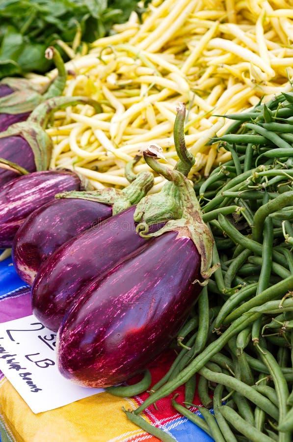 Aubergine et haricots verts à un marché local du ` s d'agriculteur photos stock