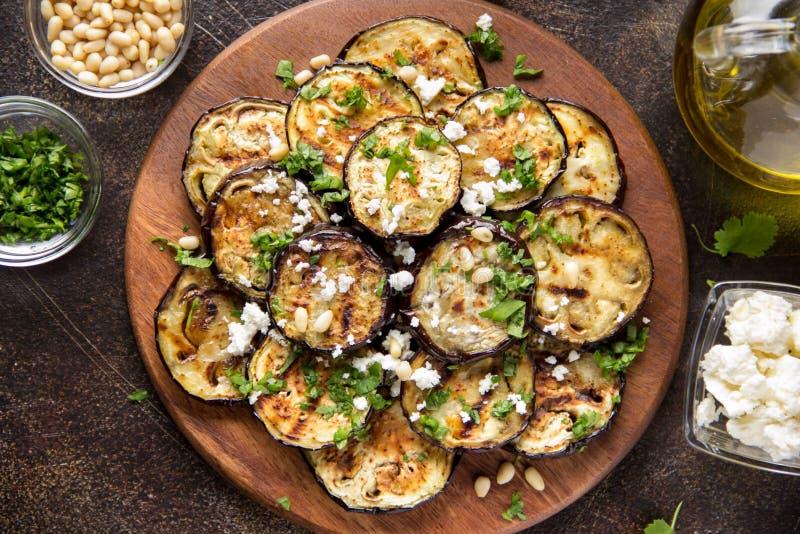 Aubergine frite avec du feta, des pignons, des herbes fra?ches (cilantro, persil) et l'huile d'olive Casse-cro?te v?g?tal savoure image stock