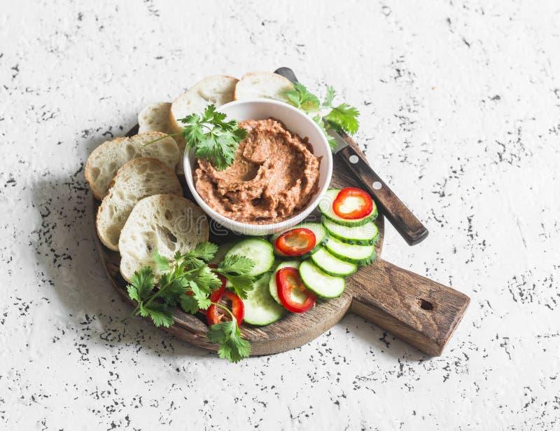 Aubergine, geräucherter Paprika, Walnüsse tauchen, Gemüse und Brot auf hölzernem Schneidebrett auf einem hellen Hintergrund ein stockfoto