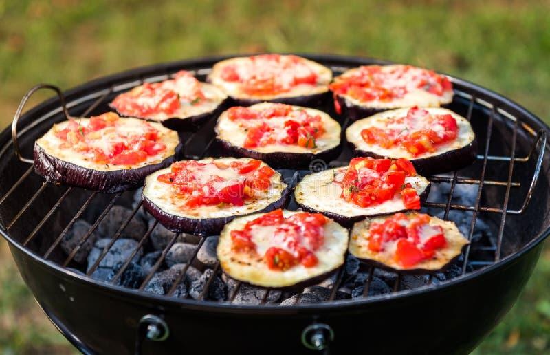 Aubergine met tomaat en parmezaanse kaaskaas bij BBQ de veganistgrill royalty-vrije stock afbeelding
