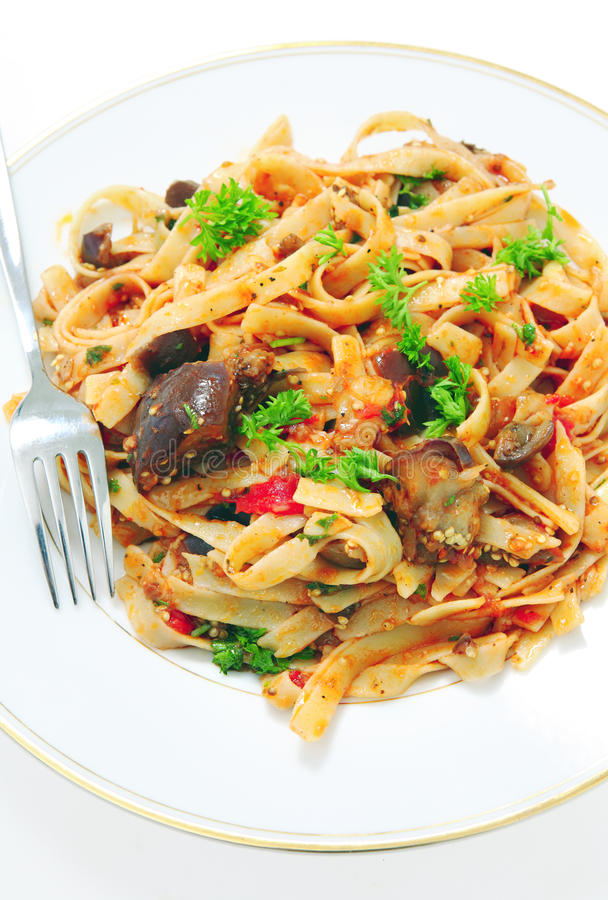 Aubergine with pasta. An aubergine (eggplant) and tomato sauce served tossed with fettuccelle pasta and garnished with fresh parsley royalty free stock photos