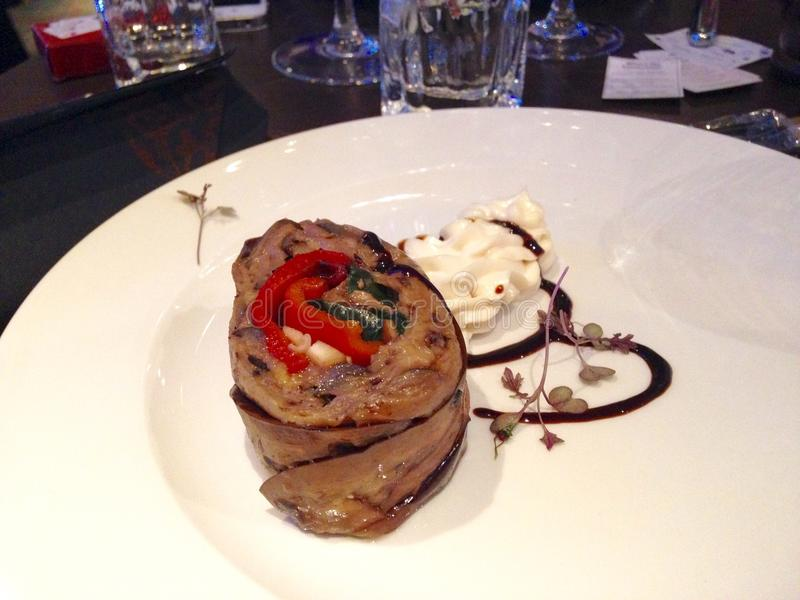 Aubergine and red pepper roulade. On the white plate stock image