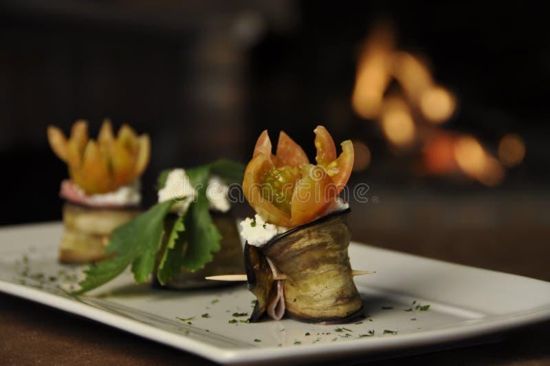 Aubergine roulade. Two aubergine roulade with garnish, sitting on a rectangular white dish stock photo