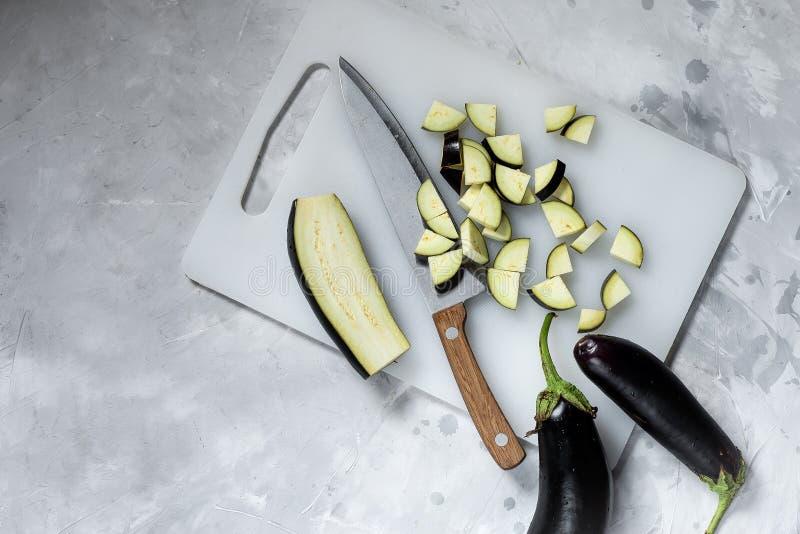 Aubergine skivad ö med en kniv in i olika stycken arkivfoton
