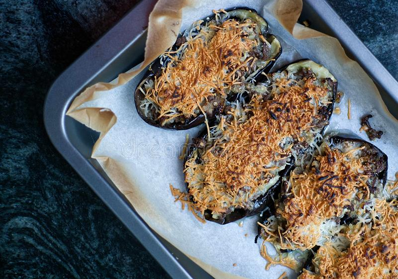 Aubergine stuffed au gratin with meat and cheese from above on a black marble table of a rustic kitchen. Empty copy space royalty free stock photography