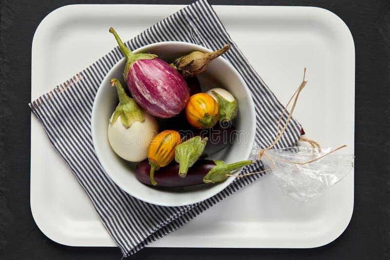 Auberginen in der weißen Schüssel auf Behälter lizenzfreie stockbilder