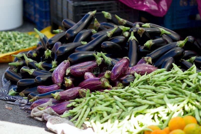 Auberginen und grüne Bohnen am Markt des Landwirts stockfotografie