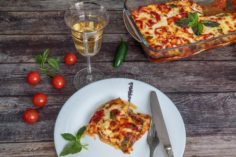 Aubergineparmezaan, een stuk op een plaat met een mes en een vork, naast het dienblad met aubergines, een glas witte wijn, kers royalty-vrije stock afbeeldingen