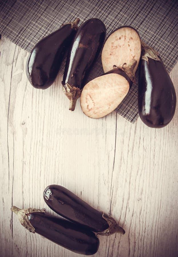 Aubergines на деревянной предпосылке стоковые изображения
