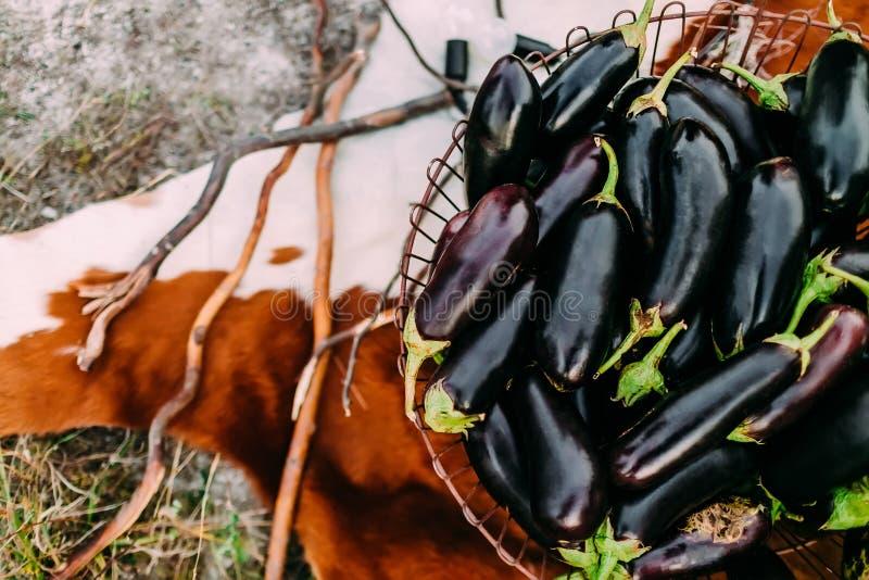 Aubergines in een ijzermand op de achtergrond van zweep stock foto's