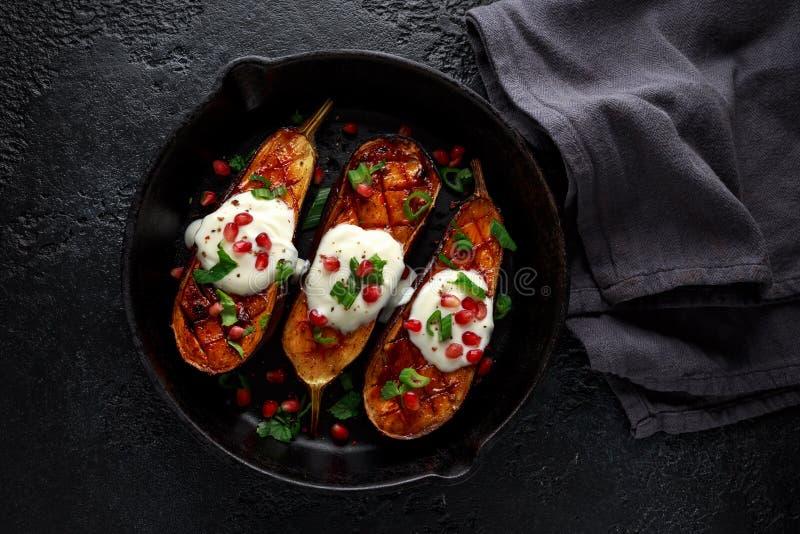 Aubergines grillées avec de la sauce à yaourt, les graines de grenade, le persil et l'oignon vert dans la casserole de cru de fon photos libres de droits