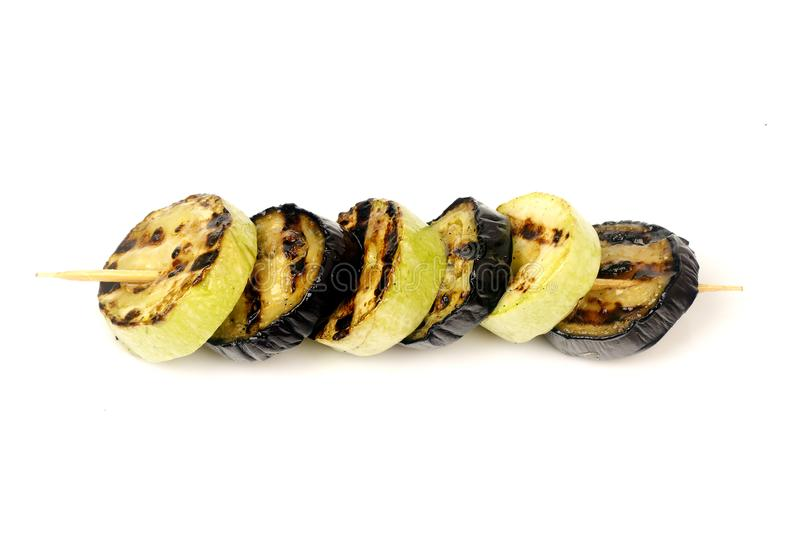 Aubergines and zucchini roasted on a grill on a spit. Aubergine and zucchini grilled on a grill on a spit on a white background for isolation royalty free stock photos
