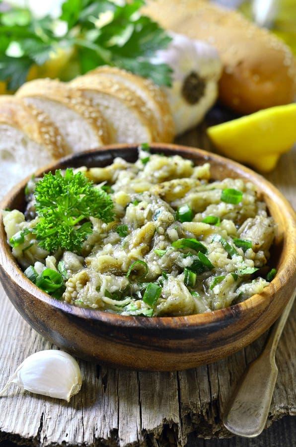 Auberginesallad med olivolja, örten och vitlök arkivfoton
