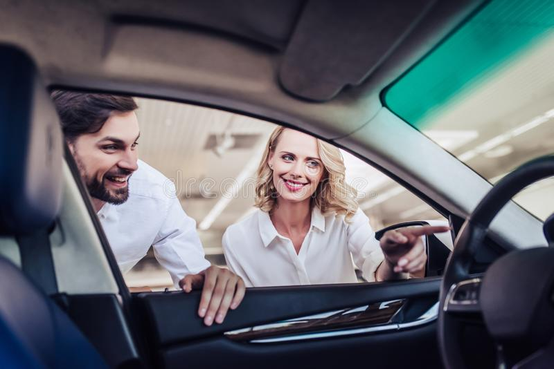 Aucasian couple looking at new car stock photos